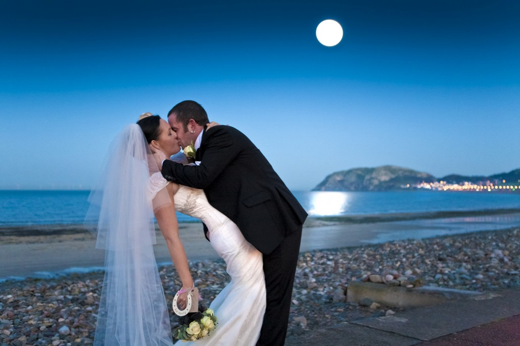 Bride and groom kiss under full moon