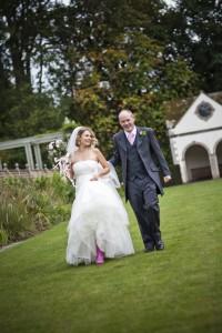Bride and groom walking across grass