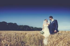 Bride and groom walk through field