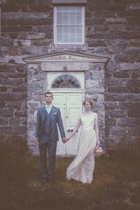 Bride and groom in front of white door