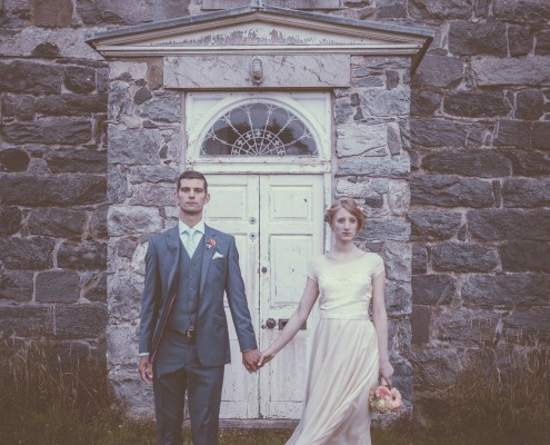 Bride and groom in front of white door