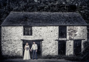 Bride and groom in front of cottage