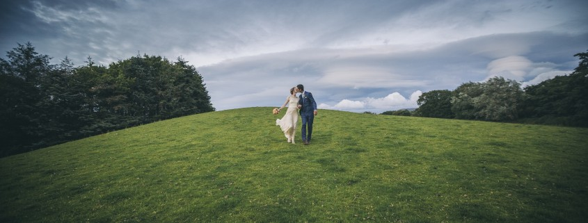 Bride and groom walking over hill