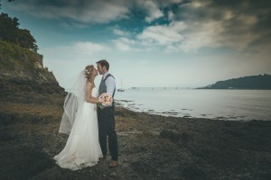 Bride and groom kiss by the water